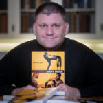 "Eric Goff holding a copy of his book ""The Physics of Krav Maga"""