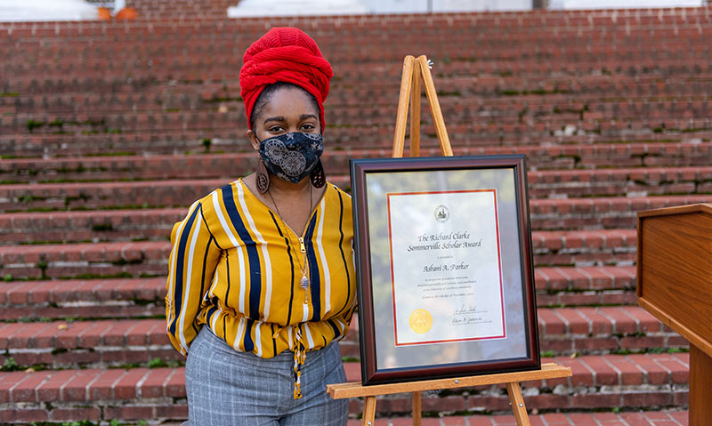 Ashani Parker stands beside her Sommerville Scholar certificate
