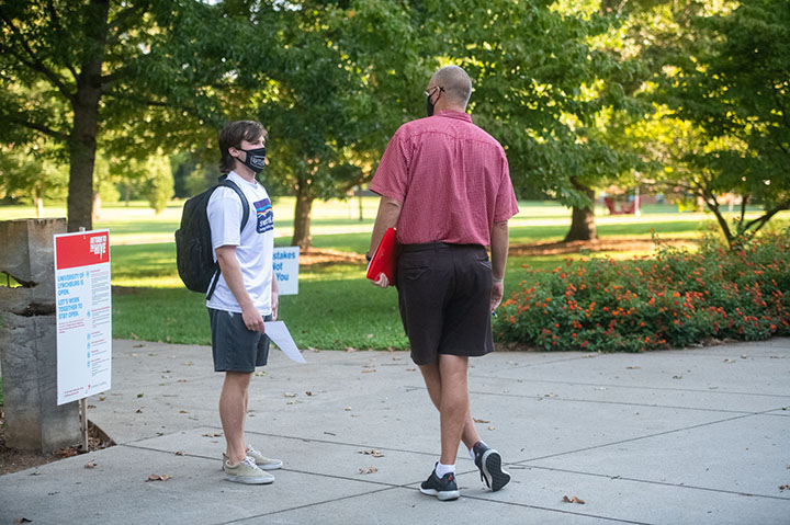 Student and professor on campus in masks
