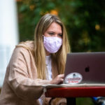 Student studying with laptop, mask