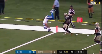 A football player performs a front flip to land in the end zone for a touch down.