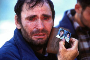 Peter Turnley photo of man holding children's photos