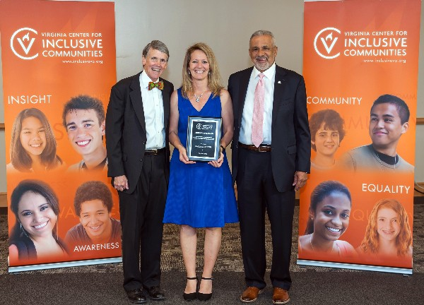 Sally Selden holding humanitarian award with two VCIC representatives. Banners behind them have the Virginia Center for Inclusive Communities logo and the words community, equality, awareness, insight.