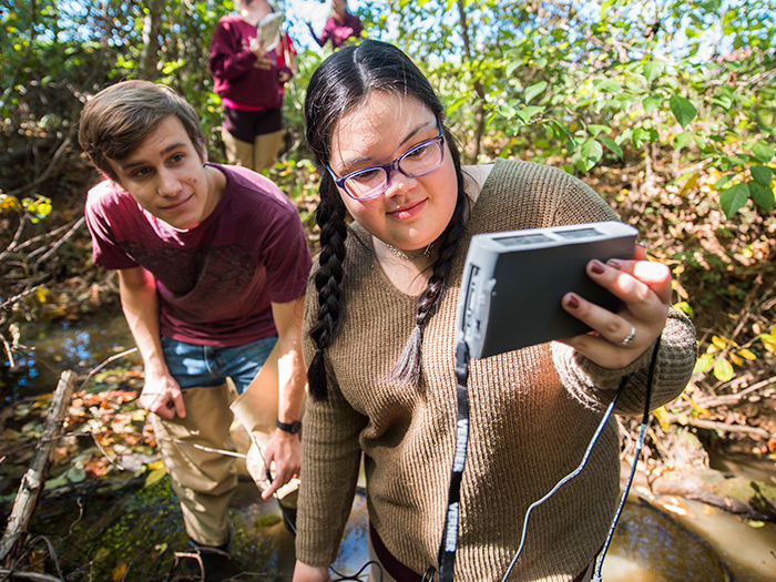 Two students standing in a creek testing water quality
