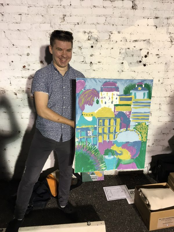 A man holds up a painting that depicts a city scene.