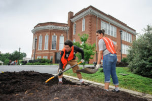 Two students shoveling mulch