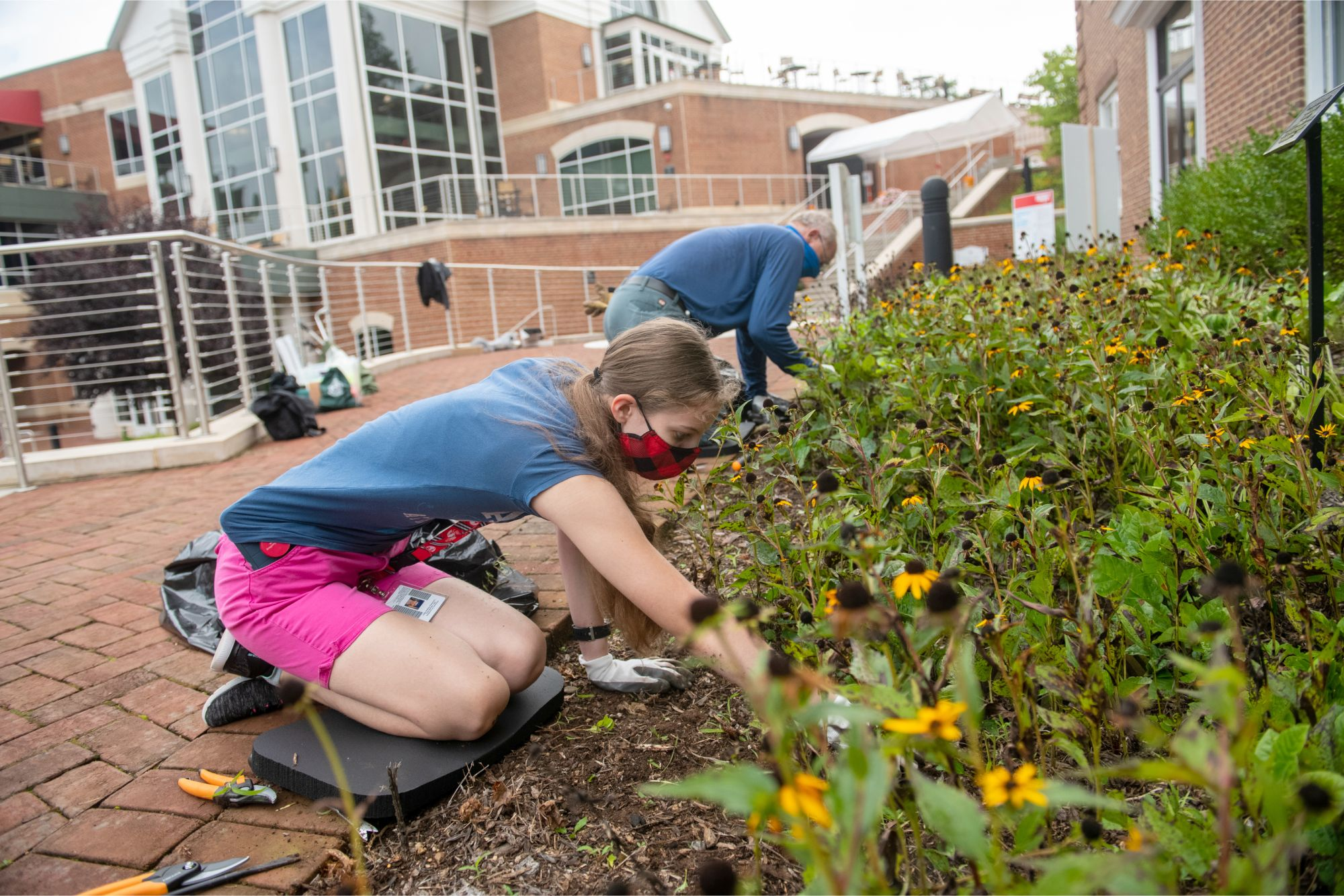 A woman works on pulling up weeds outside Drysdale Student Center