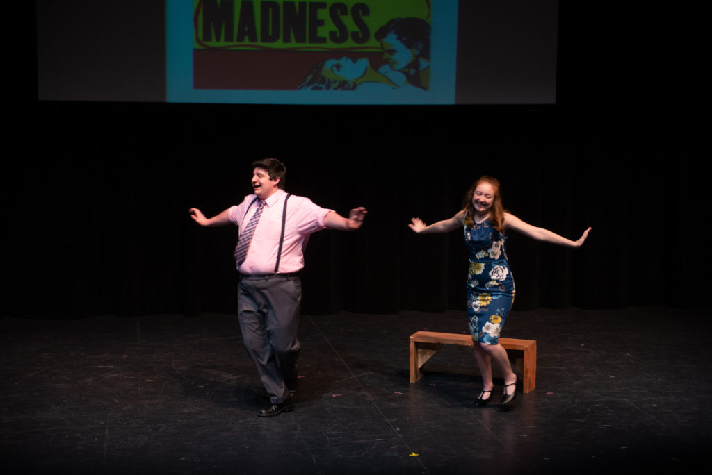 Two students dance and sing on stage
