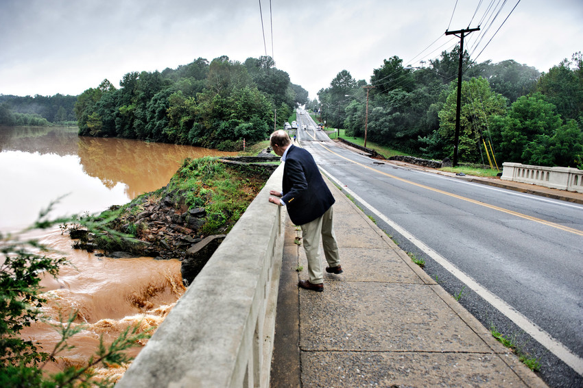 President Garren looks over the hand rail at the bridge to see the lake flowing brown over the dam