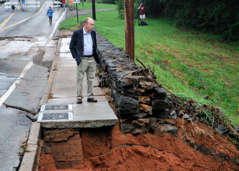 President Garren stands on damaged sidewalk by the College Lake dam