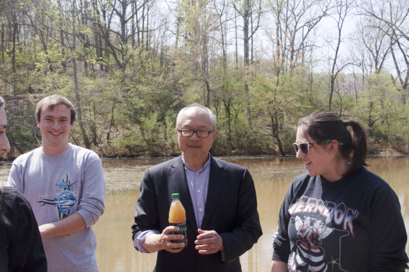 Artist Mel Chin holds a cloudy bottle of lake water and talks to two students in front of College Lake, which is brown