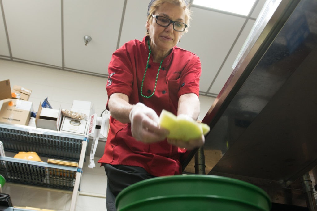 Dining services employee drops food scraps into a green bucket for compost