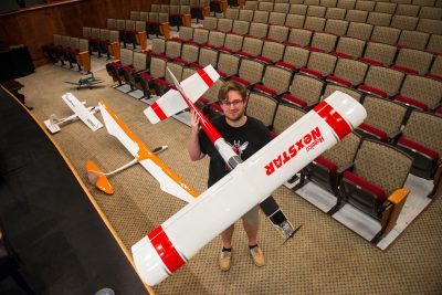 Nathan Estes holding a large model airplane.