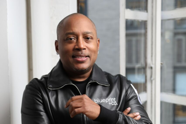 Picture of Daymond John wearing a leather Jacket and crossing his arms.