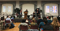 Participants on stage and audience at debate and forensics club event