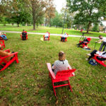 a group of faculty, staff, and students discuss diversity in red chairs on the Dell