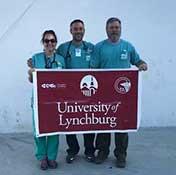 Dr. Elyse Watkins, Dr. Jeremy Welsh, Dr. Greg Davenport holding a red university of Lynchburg banner