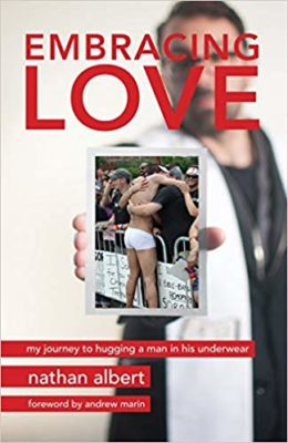 "Cover for the book ""Embracing Love."" In addition to the title, it shows Nathan Albert holding the famous photo of him  hugging a man at a Chicago Pride event."