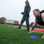 Photo of an exercise physiology student walking on Shellenberger field while a research participant is on his hands during a physical strength and endurance test.