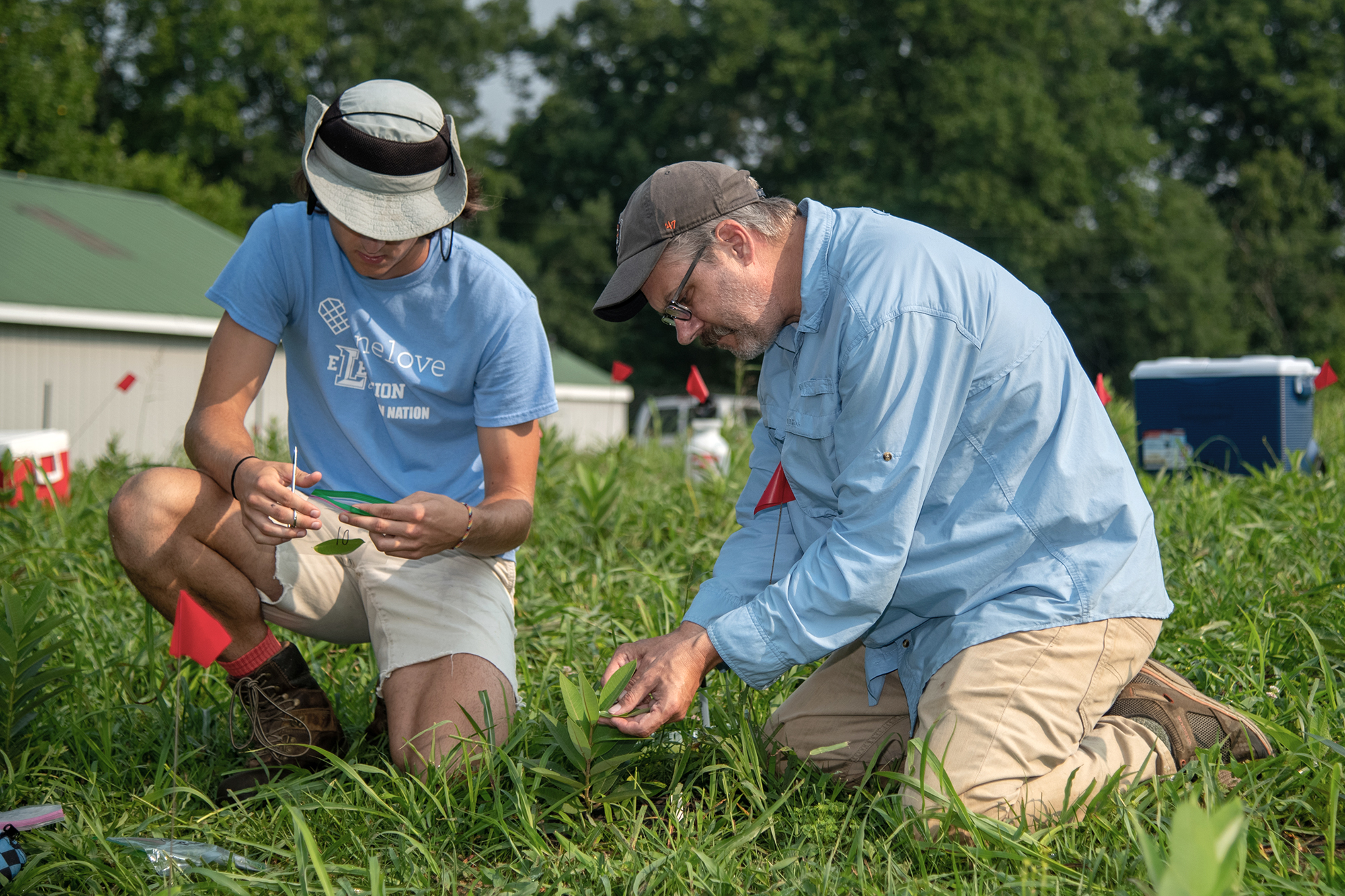 John Styrsky demonstrates for a student how to clip leaves