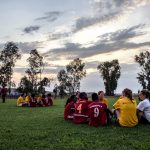 Photo of soccer players in Africa sitting on a field after a game at twilight.
