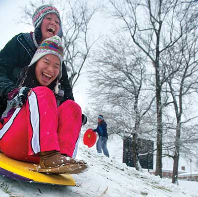 Two students sledding down an icy hill and laughing