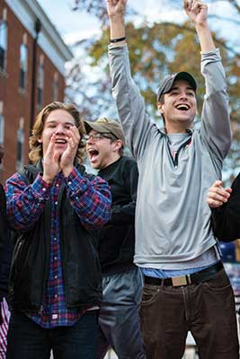 Group of three male students cheering
