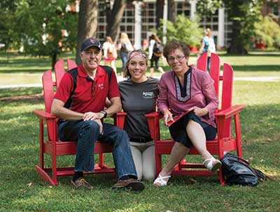 Student with parents sitting in red chairs on the Dell