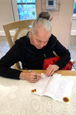 An older woman writes a letter