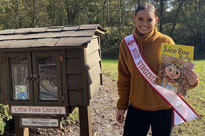 Alexis Crosen poses with two books in front of a Little Free Library