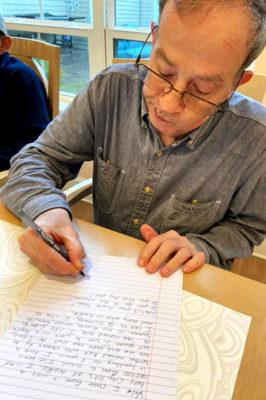 An older adult writes a letter