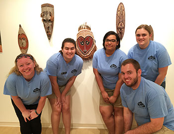 Group of museum studies students with examples of aboriginal art