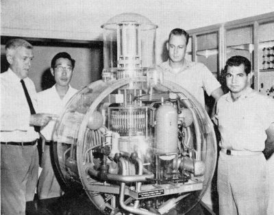 Four men gather around a model of a nuclear reactor.