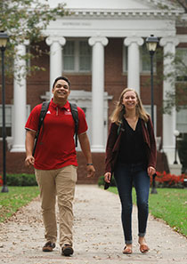 Sarah Mock and Dominic Butler walking in front of Hopwood Hall
