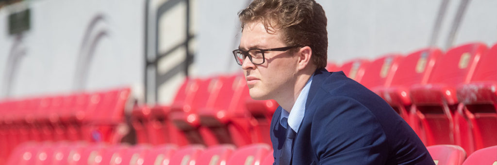 MBA in Sports Management - Person in a suit sits in the stands of a sports venue looking towards the field.