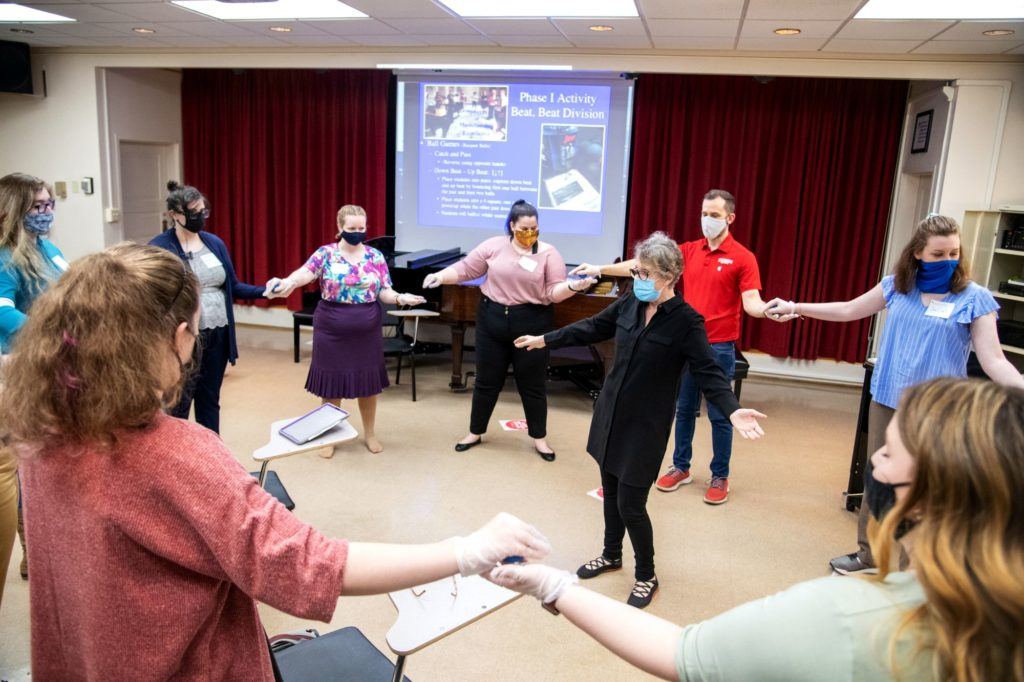 Carol Krueger leads an exercise where students hold hands in a circle