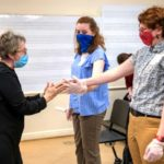 Carol Krueger demonstrates a hands-on exercise with two students holding hands