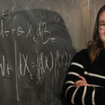 Emily Horton in front of chalkboard with equations