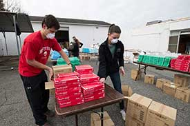 PA students stacking red boxes of PPE on a table for distribution