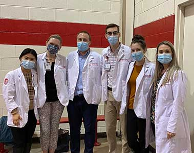 PA students and faculty in white coats at the Vaccine Climic