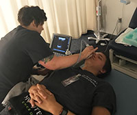 Two PA students engaged in ultrasound practicum in a lab