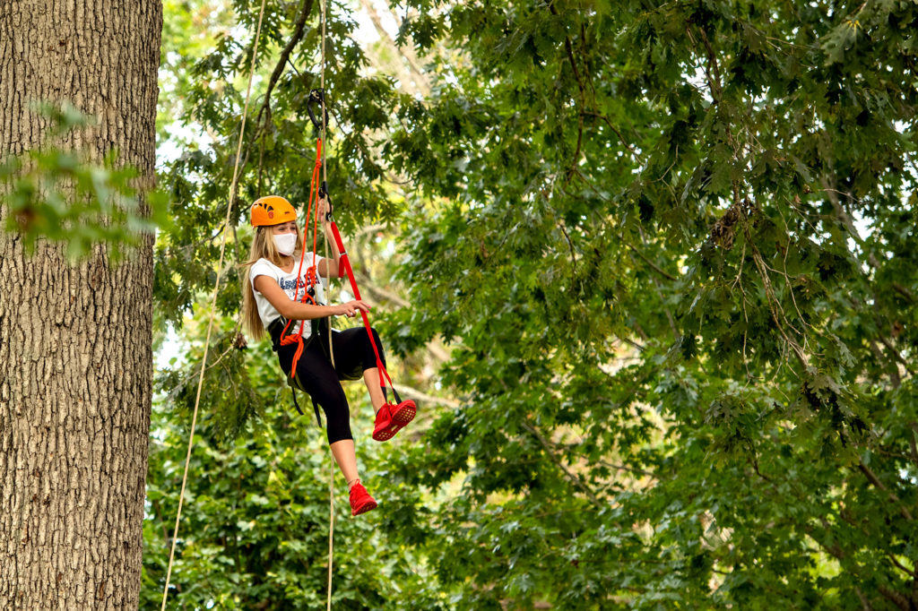 A girl flys down a zip line in the trees