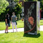 Students stand beside a tall art installation by Eli Germanotta