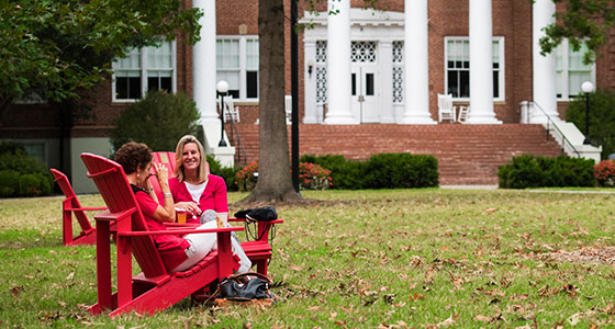 Two women sitting in red chairs in front of Hopwood Hall