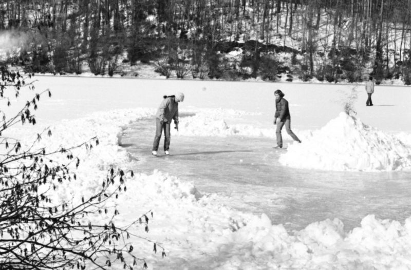 photo of people on a frozen college lake in a trench dug between snow