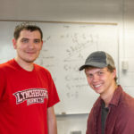 Carl Pilat and Noah Baumgartner in front of a whiteboard with equations written on it