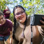 Students look at a monitor during water sampling