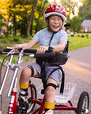 Child smiling and riding a bike